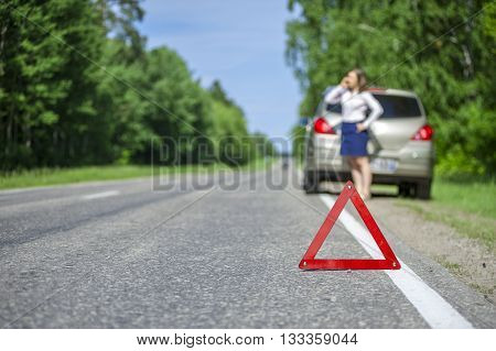 Young woman calling for car assistance after breakdown on the road. Focus on red triangle warning sign.