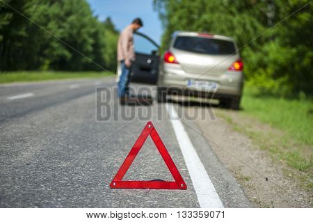 Broken car and male driver with spare wheel. Focus on red triangle warning sign.