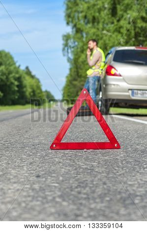 Red emergency sign on the road male driver calling to a car assistance spare wheel near broken car.