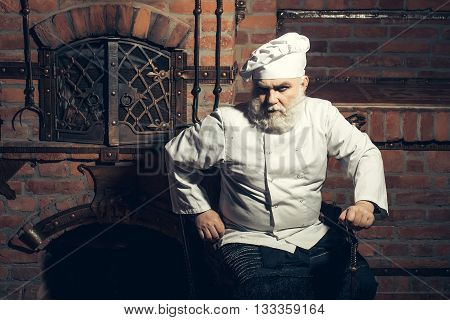 Senior Cook Sits At Oven