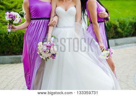 Bride, row of bridesmaids with bouquets at big wedding ceremony. Big wedding bouquets