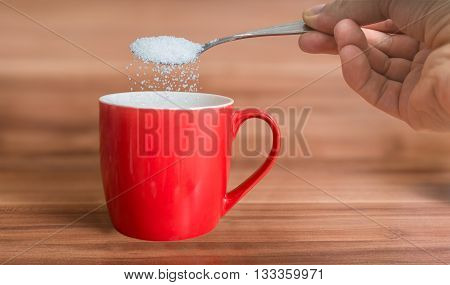 Hand Is Pouring Sugar To Red Cup Of Tea. Unhealthy Eating Concep