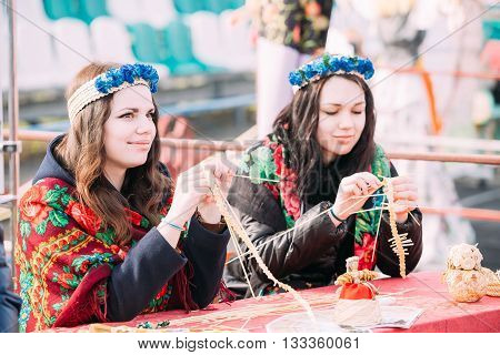Gomel, Belarus - March 12, 2016: Beautiful young women busy creating souvenirs from straw at Celebration of Maslenitsa Shrovetide holiday.