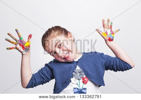 Little girl with arms raised showing painted hands on grey background