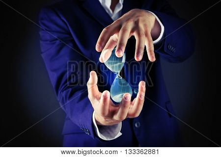 Businessman holding hourglass in hands on dark background