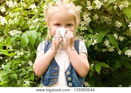 girl has a runny nose. flowers pollen allergy