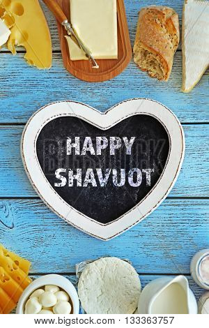 Text happy Shavuot in frame of fresh dairy products on blue wooden table
