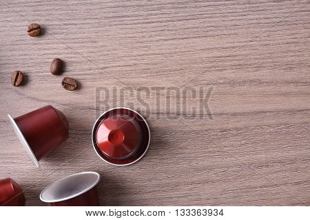Three Capsules Espresso Coffee On Wooden Table Top View