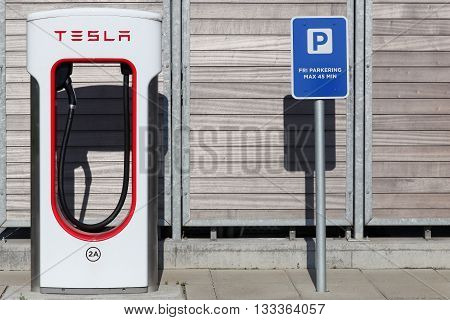 Aabenraa, Denmark - June 4, 2016: Tesla supercharger station and parking. Tesla is an American automotive and energy storage company that designs, manufactures, and sells luxury electric cars
