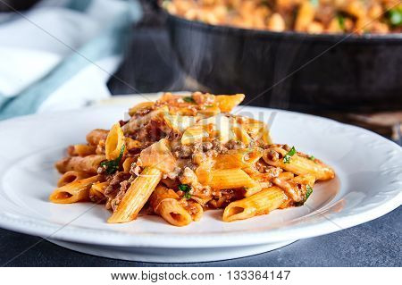 Close up of american chop suey - pasta dish with beef, tomato sauce, mozarella cheese, spices and parsley. Italian-American cuisine. White plate with steaming hot pasta and pan with rest dish on back