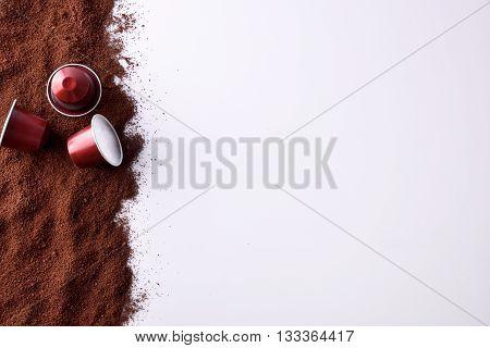 Three Capsules Of Espresso On Ground Coffee Top View