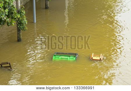 A garbage container and various wooden things are floating on the River Seine embankment after the massive flooding in Paris during the first days of June 2016.