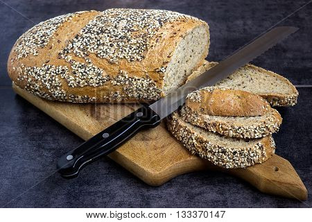 Whole wheat bread and rye sprinkled with sunflower seeds poppy seeds sesame seeds sliced with a knife on a board