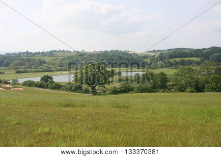 This photo shows the beauty of country side of Wales. Everything is breathtakingly beautiful. Green plants. Lake. And curvy hill.