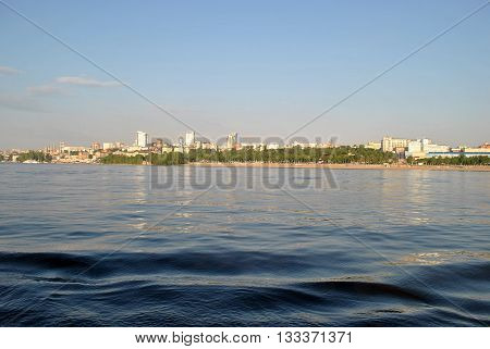 Panorama of the city of Samara with the Volga river, in the summer, against the sky. The water and waves in the foreground. Evening lighting. Russia. Viewing city blocks of the waterfront.