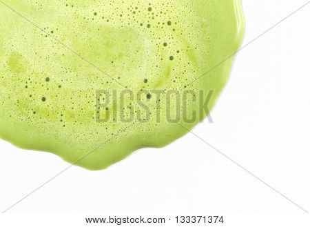Background of close focus on melting green tea ice cream with small air bubble on surface. It melt and flow on white background beside of blank space on the right.