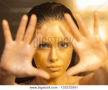 Portrait of beautiful woman with golden makeup and bodyart and outstretched forward arms. Focus on the face.