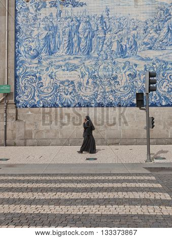 PORTO PORTUGAL - MAY 26 2016: A nun walking by near Carmo Church in the historical center of Porto Portugal