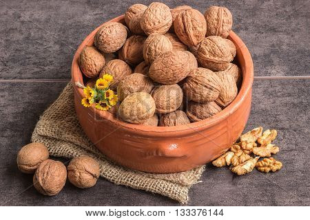 Walnuts in a ceramic bowl and a small bouquet of wild flowers on a dark background