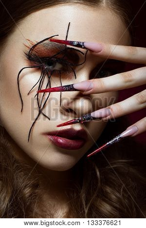 Portrait of woman in the image of spider with creative art makeup and long nails. Manicure design, beauty face. Photos shot in studio