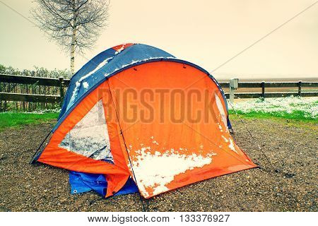 Orange Touristic Tent With Snow. Tent On Sand, Snowy Green Grass