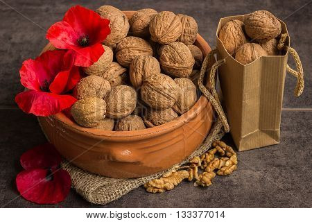 Walnuts in a ceramic bowl and red poppies on a dark background