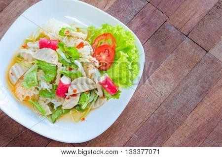 Thai cuisine spicy pork salad on wood background or Yum Moo Yor