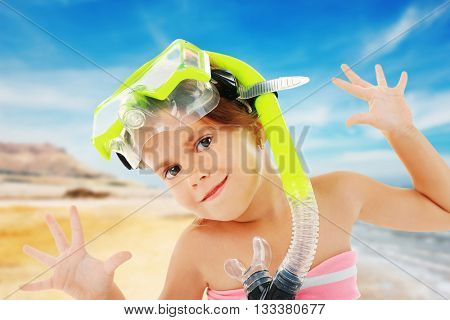 Funny little girl with yellow diving mask on blurred resort background