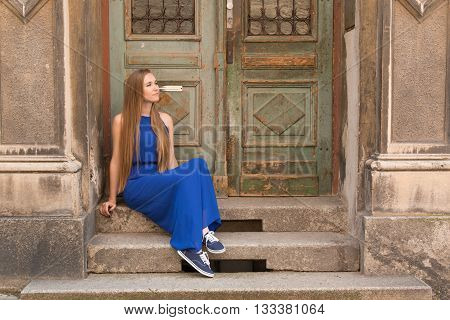 Modest young girl on the background of the old wall with door
