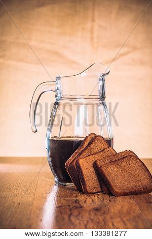 Russian Brew In Jug  And Loaf Of Rye Flour On Wooden Background