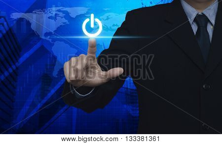 Businessman pressing power button over map and city tower Elements of this image furnished by NASA