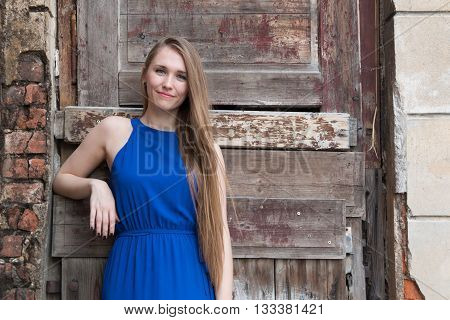 Modest young girl on the background of the old wall with wooden door