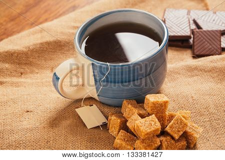 Blue Cup Of Tea And Lump Sugar On Sacking Background
