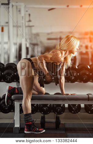Classic bodybuilding. Muscular blonde woman doing exercises in the gym