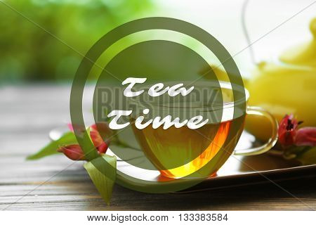 Text Tea Time and glass cup of tea with teapot on wooden table against blurred background