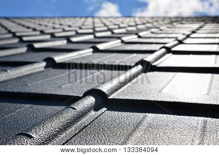 new roof with black sheet metal and background of blue sky