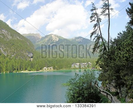 view on the Lake Braies and a hotel, surrounded by the peaks of the Braies Dolomites in South Tyrol, Italy; blue sky and white clouds, hiking area
