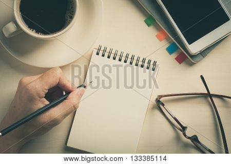 Young man left hand writing on blank notebook on wood table with coffee cup smartphone and glasses beside in morning time with vintage filter effect