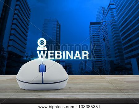 Wireless computer mouse with webinar icon on wooden table in front of city tower background Seminar online concept