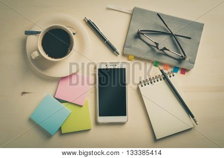 Opened notebook and pencil on wood table with coffee cup smartphone with blank area on touchscreen sticky paper and glasses beside in morning time with vintage filter effect