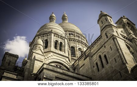 PARIS, FRANCE - MAY 17, 2016:  Opened in 1914, Sacre-Coeur Roman Catholic Basilica was dedicated to the Sacred Heart of Jesus. This cathedral is a major tourist attraction with its huge rounded domes and beautifully detailed facade
