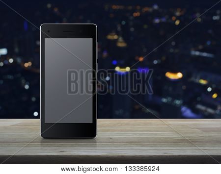 Modern smart phone with blank grey screen on wooden table in front of city tower background