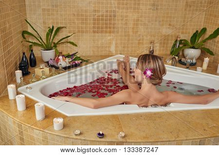 Woman relaxing in jacuzzi with rose petals