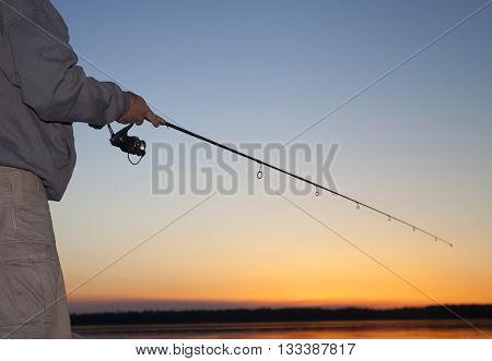 Spinning reel in the hands of an angler at sunset at Saskatchewan Canada