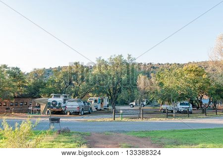 MOUNTAIN ZEBRA NATIONAL PARK SOUTH AFRICA - FEBRUARY 18 2016: Tents a caravan motorhome and vehicles at the camping grounds in the Mountain Zebra National Park near Cradock at sunset