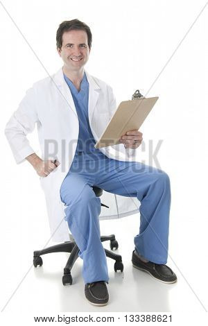 Full length image of a physician in scrubs and lab coat, looking at the viewer as he sits on his rolling stool with a clipboard in hand.  On a white background.