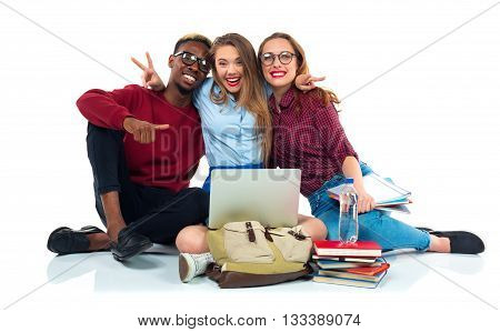 Three happy young teenager students sitting with books laptop and bags isolated on white background