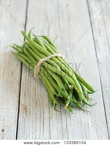 Fresh green french beans on a wooden background