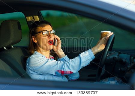 Businesswoman multitasking while driving drinking coffee and talking on the phone