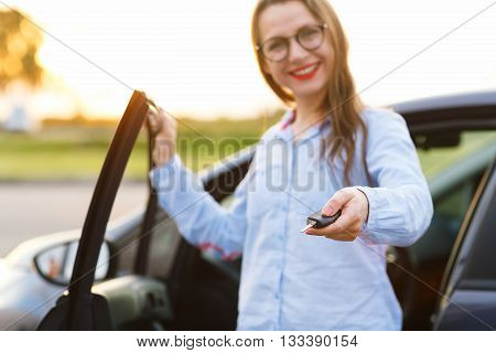 Young woman standing near a car with keys in hand - concept of buying a used car or a rental car